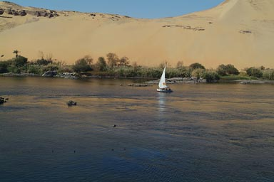 Lone felucca, blue Nile at Aswan, desert dunes in back.