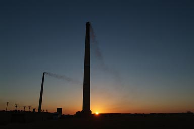Brick burning chimneys, Dakhla oasis town, sunrise behind, southern Egypt.
