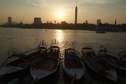 Nile and pleasure boats, Cairo tower, smoggy sunset.