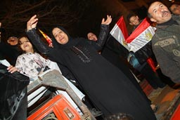 Muslim Egyptian woman celebrating football team's victory in streets of Cairo.