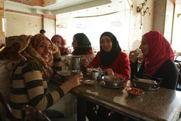 Veiled Muslim girls, eating kushari, Cairo.