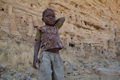 Dogon boy, in front of old Tellem and Dogon settlements in Dogon Escarpement, Irelli.