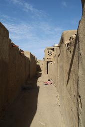 Narrow alley in Sanga, two kids play in dust. Dogon Country.