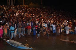 Crowd standing in water. Segou Festival.