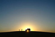 Land Rover on dune, sun sets behind.