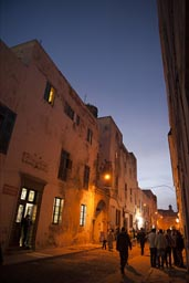 Essaouira, small street light lit alley at night, people strolling, sky dark blue.