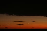 New new-moon, on orange sky, black clouds above and below.