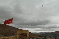 Bayburt, snow on mountains, view from castle, Turkish flag and crows.