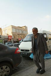 Old man, baggy trousers, plastic bag, Mardin, Turkey.