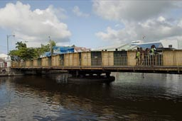 The hand operated, turning main bridge in old Belize City. Caribbean girls.