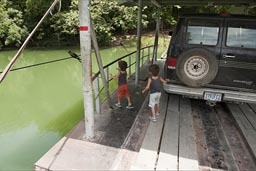 Hand pulled ferry over Mopan River to Xunantunich. 2 little boys and a van on it. Belize.