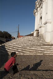 Saint Thomas church, Chichicastenango late light on steps, shoe cleaner boy in red. Guatemala.