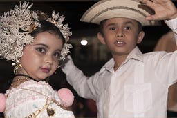 Little boy and hat, little carnival girl with head gear and dress and gold and all, pose. Carnival Panama, Las Tablas.