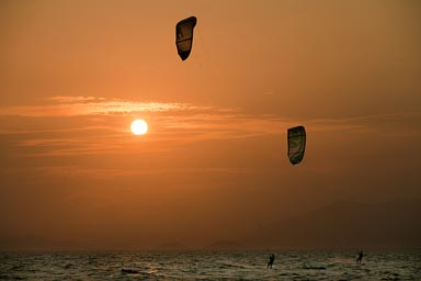 Kite surfers, Punta Chame, under an orange sunset, Panama. Pacific Ocean.