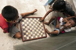Children playing board game San Ignacio/Tupiles, Guna Yala. Panama.