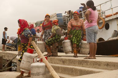 Guna women carry away gas-bottles, from commercial ship, docked on Ustupu, Guna Yala island.