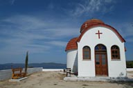 Little, white Chapel, against blue sky and water, Greece.