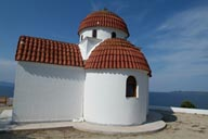 Small, orthodox greek white chapel, blue sea and sky.