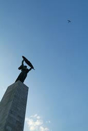 Citadella communist statue and small aircraft in blue sky.