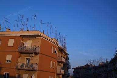 Antennas on a roof, nightly sky.
