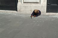 Begging old woman on pavement, Rome.