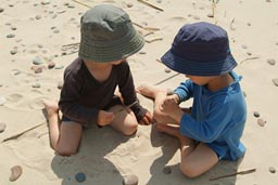 Boys in hats on Latvian beach watch a bug on a stick.