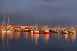 Red boats in the harbour of Bodo, Norway, lit by midnight sun.