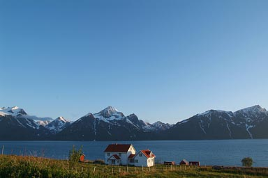 Lyngen mountains, midnight sun, white house in front of Fjord, Norway.