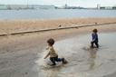 Twins in St. Petersburg, gumboots in puddle, beach and waterfront in back.
