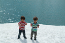 Boys on snow, turquoise lake, Styrn, Norway.