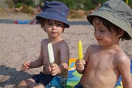 Twins, hats, ice cream on beach.
