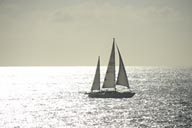 Sailboat on sunlit ocean, Southern California, sun white reflections.