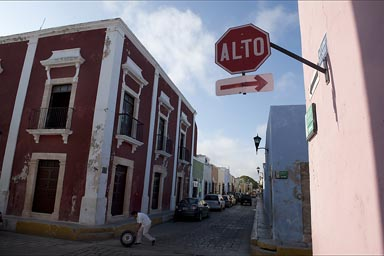 Stop/Alto Sign and Street Corner, old town Campeche, man rolling a tire.