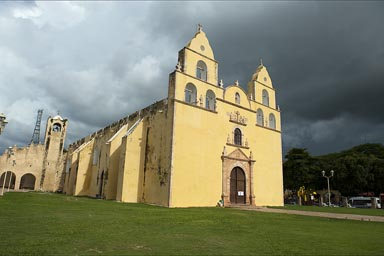 Dark clouds towering over bright yellow Oxkutzcab church.
