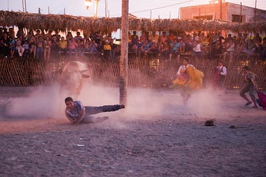 One torero in bullfight in Yucatan, Mexico, goes down, twilight.