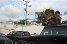 Boys get bored after a while, climb top of van, in garage in Cancun.