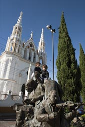Boys on top of mariachi sculpture in front of white San Jore church in Comitan, Chiapas. Blue sky.