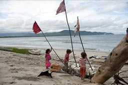 Raising fishing net boyes and the flags on poles, boys and girls on dunes of Chipehua, Mexico.