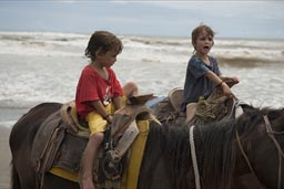 Boys are riding horses on Pacific Beach.