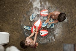 Washing the sand off in rain water, pours from the roof. Zipolite, twin boys.