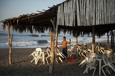 Raking a beach cafe, early morning. Puerto Arista.
