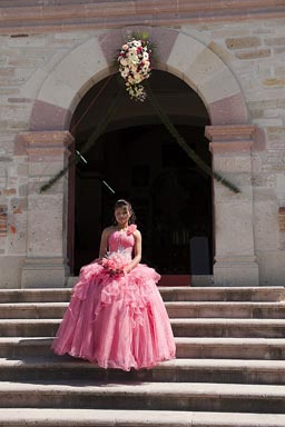 Rose Mexican girl, her 15 year celebrations (fiesta de quince anos) dressed in rose wedding dress, on steps of San Pedro church in Mitla, Oaxaca..