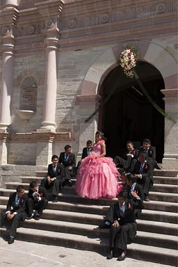 Quinceaneras, possible grooms surround 15 year old Mexican girl.