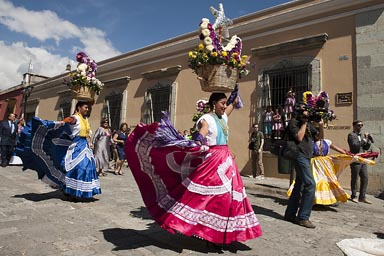 Women carrying flowered baskets. Marriage parade Oaxaca.