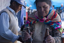 Old indigenous woman brings two bottles of beer, Coipasa, Bolivia.