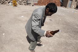Drunk and dancing with a bottle of beer, man Coipasa, Bolivia,