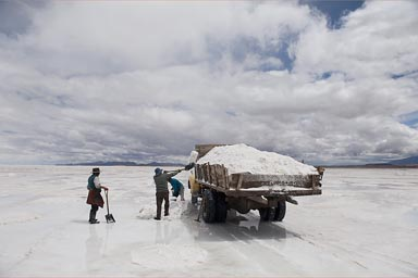 Men with shovels load an old truck on the Salare de Uyuni, Bolivia, with wet salt that sells for 4 B$ the 50 kgs.