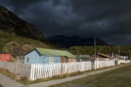 Dark clouds, low evening sun lights wooden houses and white fence in Villa O'Higgins.