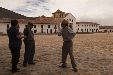 Men discuss and joke on plazza of Villa de Leyva.