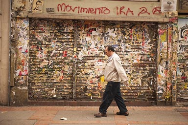Man walks in front of shabby shop front, Bogota.